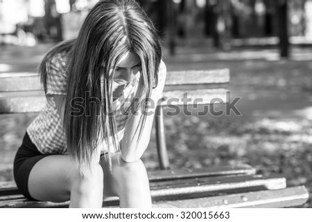 sad woman sitting on bench in a park, black and white photography - stock photo