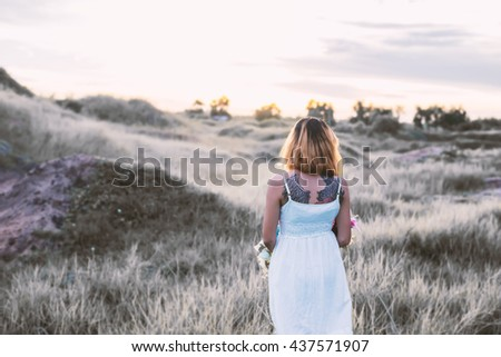 Sad woman walking alone at meadows,loneliness - stock photo