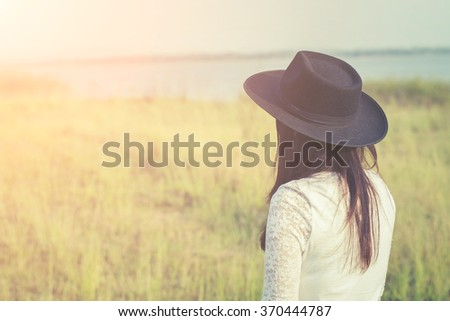 sad woman wearing black hat standing in a meadow  - stock photo