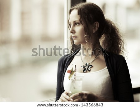 Sad woman with cocktail looking out the window - stock photo