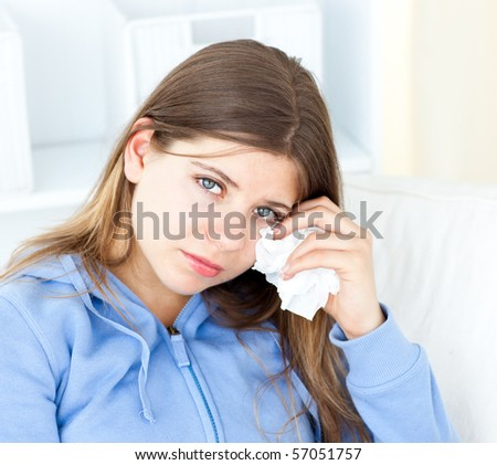 Sad woman with tissues looking at the camera - stock photo