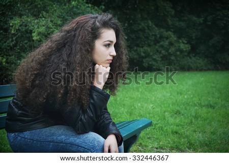 sad youn woman sitting on park bench - stock photo