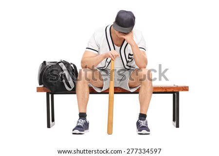 Sad young baseball player sitting on a bench and contemplating with his head down isolated on white background - stock photo