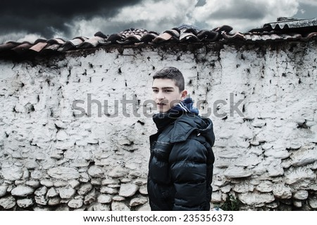 sad young boy before loam wall - stock photo