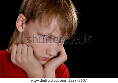 sad young boy in red on a black background - stock photo