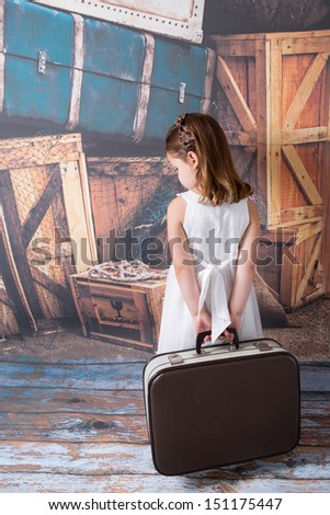 Sad young child holding a suitcase - stock photo