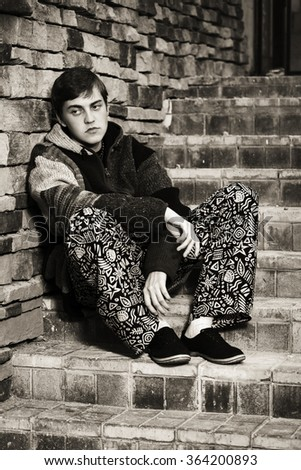 Sad young fashion hippie man sitting on the steps - stock photo