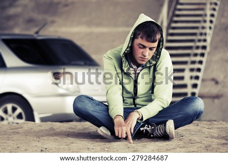 Sad young fashion man sitting on the ground outdoor - stock photo