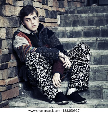 Sad young fashion man sitting on the steps - stock photo
