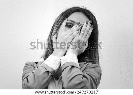 Sad young fashion woman at the wall  - stock photo