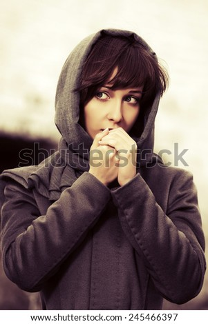 Sad young fashion woman in grey classic coat outdoor  - stock photo