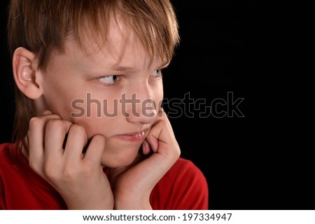 sad young guy in red on a black background - stock photo