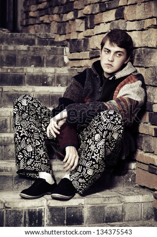 Sad young hippie man sitting on the steps - stock photo
