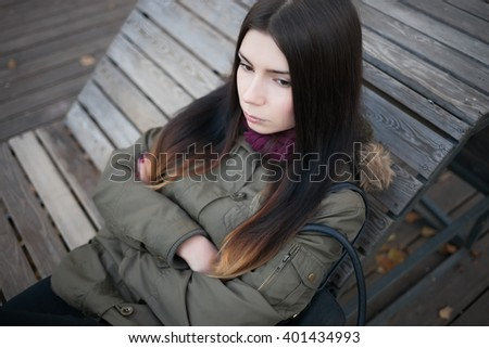 Sad young hipster girl in grey parka coat sitting on a bench with serious expression. Not happy photo - stock photo