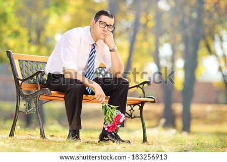 Sad young man holding a bouquet of flowers and sitting on a bench in a park - stock photo