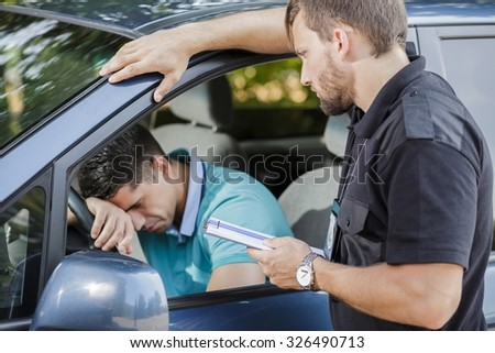 Sad young man in car fined by police officer - stock photo