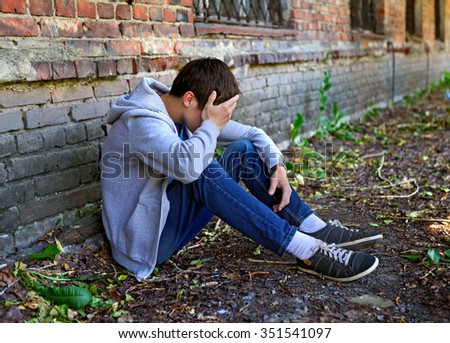 Sad Young Man near the Brick Wall of the Old House - stock photo