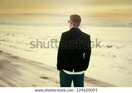 sad young man on the road and looking at the sunset - stock photo