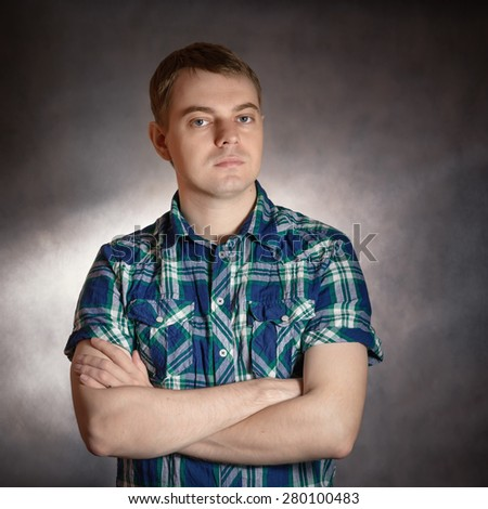 Sad young man, portrait on the dark background. - stock photo