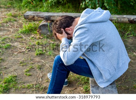 Sad Young Man sit on the Log outdoor - stock photo