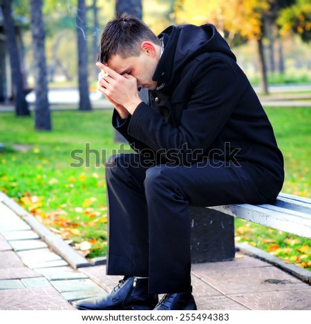 Sad Young Man with Cigarette in the Autumn Park - stock photo