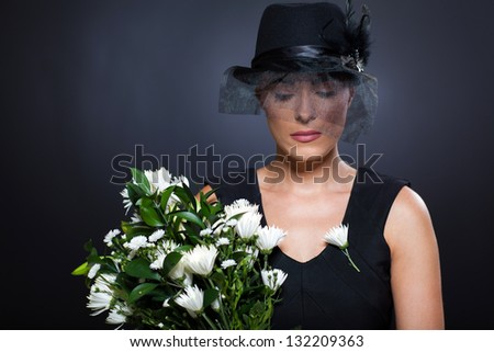 sad young widow with black mourning hat and flowers - stock photo