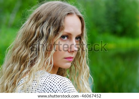 Sad young woman against nature background. - stock photo