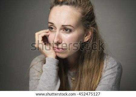 Sad young woman close up tears running down face looking in despair hand resting on chin looking - stock photo