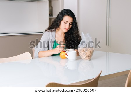 Sad young woman having breakfast in a modern kitchen - stock photo