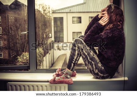 Sad young woman is sitting on the windowsill - stock photo