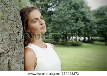 sad young woman leaning against tree with retro filter effect                              - stock photo