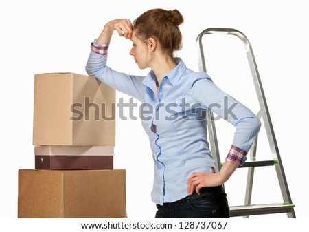 Sad young woman near a pile of boxes on white background - stock photo