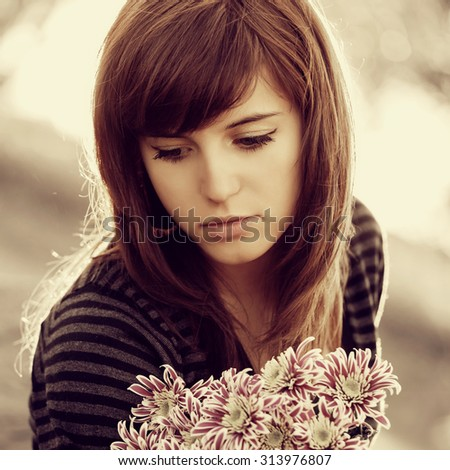 Sad young woman with a flowers outdoor - stock photo