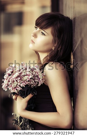 Sad young woman with a flowers standing at the wall - stock photo