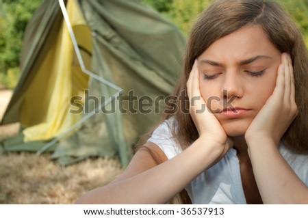 Sad young woman with collapsing tent in background. - stock photo