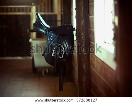 Saddle is hanging inside the horse stable - stock photo