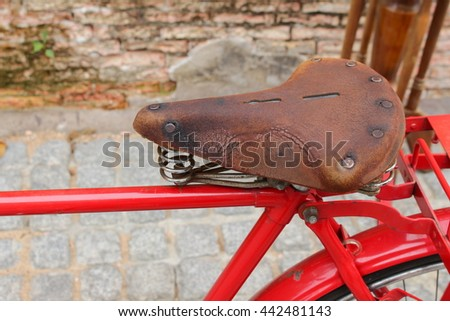 saddle leather vintage Close up of red bicycle near the window of old brick wall home background - stock photo