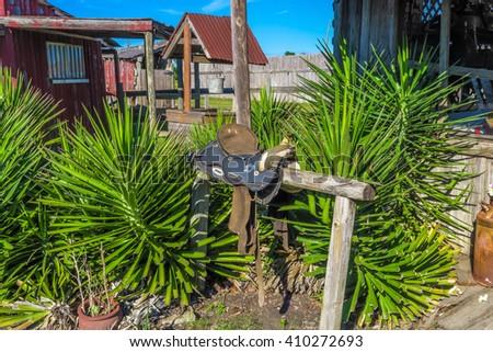 saddle on a hitching post - stock photo