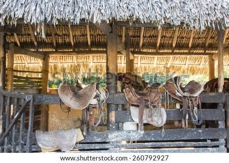 Saddles sit on a fence in the Caribbean  - stock photo
