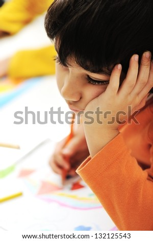 Sadness schoolboy thinking and painting. - stock photo