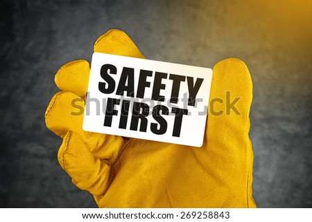 Safety First on Business Card, Male Hand in Yellow Leather Construction Working Protective Gloves Holding Card with Rounded Corners. - stock photo