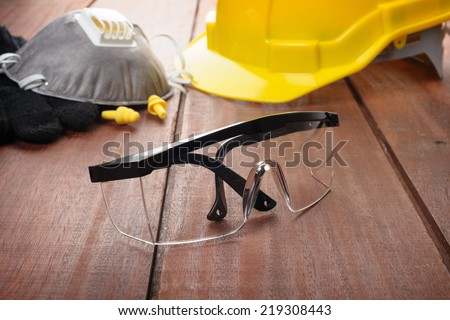 safety glasses on wooden plank - stock photo