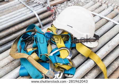Safety helmet and harness at a construction site - stock photo