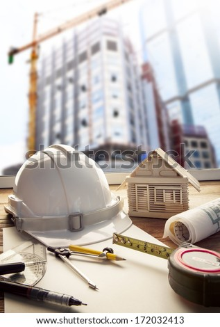 safety helmet blue print plan and construction equipment on architect ,engineer working table with building construction  crane background use for construction industry business and civil engineering - stock photo
