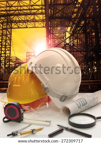safety helmet on engineer working table against pipe line structure in heavy petrochemical industry estate - stock photo