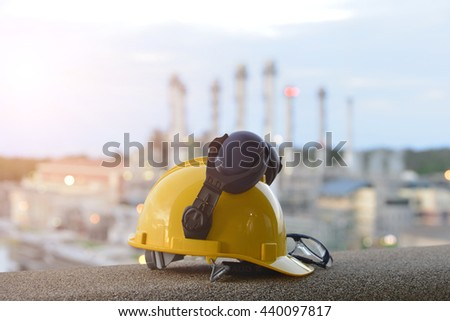 Safety in Refinery Concept , Hard hat on working table in oil refinery plant heavy petrochemical industry estate use for energy , power , fuel ,gas and fossil petroleum topic - stock photo
