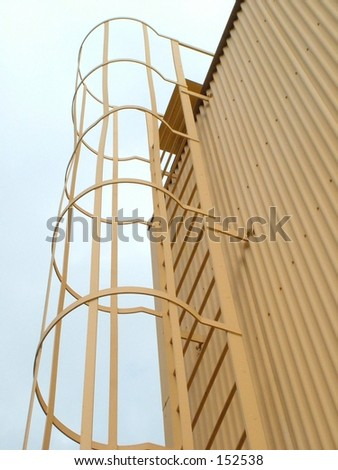 Safety Ladder going up side of building - stock photo