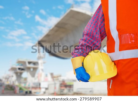 Safety Protective Work Equipment. Worker in orange vest holding yellow helmetagainst construction site as background - stock photo