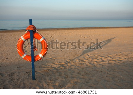 Safety ring on beach on sunny morning - stock photo