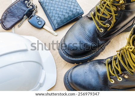 safety shoe and safety helmet,wallet,car Key on Brown Background - stock photo